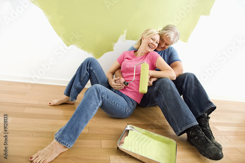 Happy couple with painting supplies