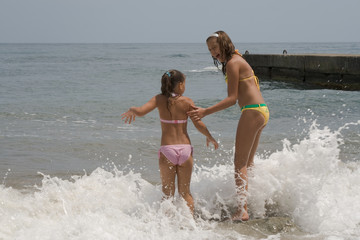 two girls of teenager make merry during a gale at the  seaside