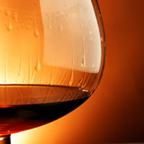 Snifter glass of cognac close-up over yellow background