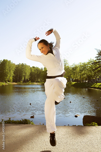 Young sporty woman jumping in front of lake