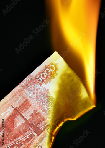 5000 russian rubles bill on fire over black background