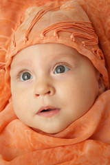 baby in orange scarf