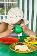 Little girl in big hat eats sweets and drinks tea