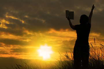 female praying with bible against summer sunset,