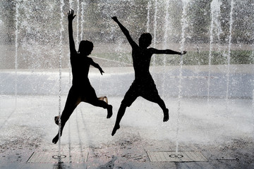 happy children jumping in fountain