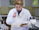 Female researcher reading something in a textbook poster
