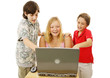 A group of kids having fun using a laptop computer.  Isolated