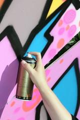 Spayer mit Sprühdose sprüht Graffiti