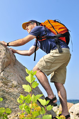 Middle aged man with backpack climbing a rock