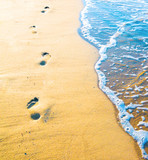 Footprint on sand with foam poster