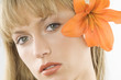 of a young pretty woman with an orange lily between hair