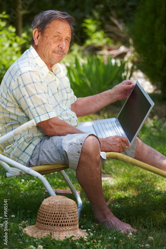 Healthy senior man is his elderly 70s using laptop computer