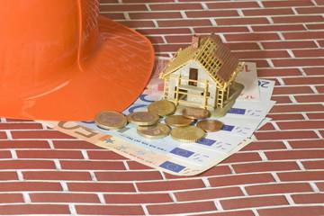 Modellhaus mit Banknoten und Bauhelm
