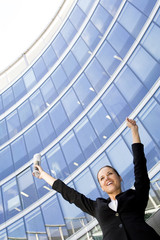Businesswoman Raising Arms at Skyscraper