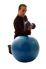 Businessman using a yoga ball and weights