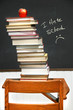 Stack of books on an old school desk with blackboard
