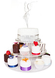 Fancy little celebration cakes, on a tiered cake stand. poster