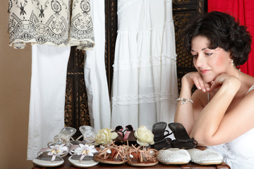 Woman with short brown hair sitting next to her shoe collection