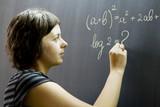Teacher writing math formulas on blackboard poster