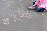 child  with chalk on asphalt poster