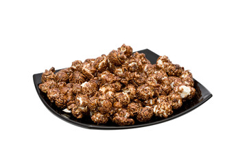 chocolate popcorn on the black plate isolated on white