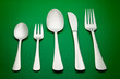 arrangement of table silverware over green background