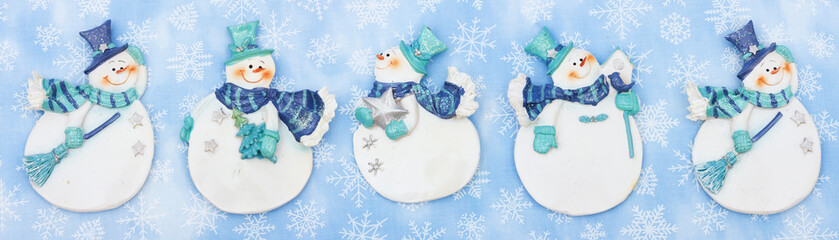 Snowmen with snowflakes on blue background