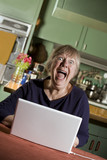Shocked Senior Woman in Dining Room with a Laptop Computer poster