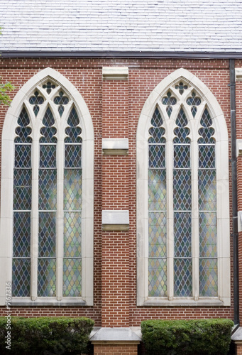 Two stained glass windows in brick wall of church