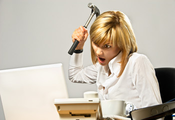 Angry business lady hitting a laptop with a hammer.