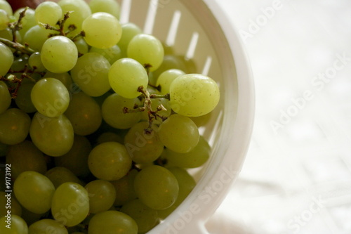 White bowl full of green grapes, copy space on right..