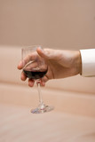Man's hand keeps a glass with a red wine on light background