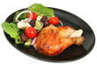 Roast chicken with a Greek salad, on a black plate