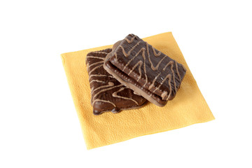 Two chocolate pastry lying on yellow paper napkin