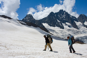 Couple of backpacking tourist on glacier in mountains