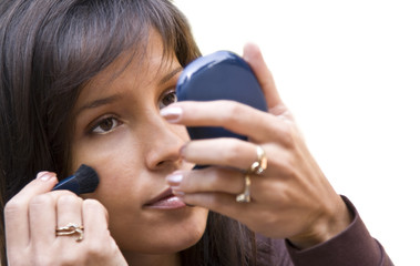 Closeup image of a woman applying powder on her face.