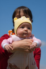 Baby with mom on blue sky background