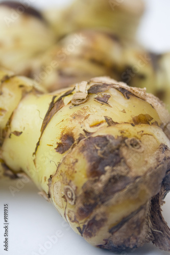 A stack of galangal root isolated against a white background