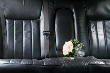 Bunch of white roses at black leather seat of newlywed limo.