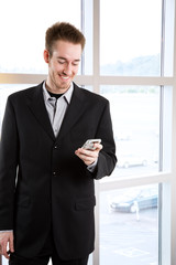A happy caucasian businessman receiving a text message