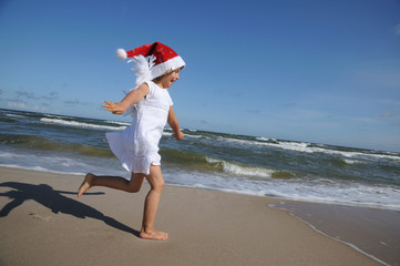 Cute Christmas Angel on the sandy beach