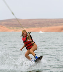 Pretty girl wakboarding with beautiful Lake Powell