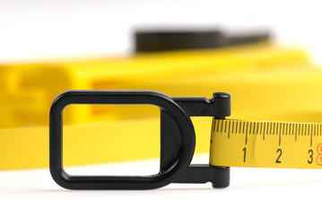 Closeup of yellow measuring tape with black plastic hook.