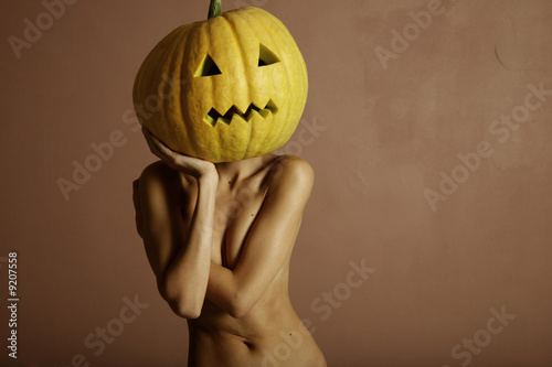 Sexy lady with big pumpkin on head. Surrealstic portrait.
