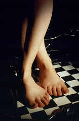 Feet of a woman on chess board with black background
