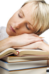 tired young woman sleeping on a stack of books