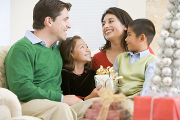 Family Smiling At Each Other,Holding Christmas Gift