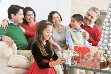 Family Sitting On Sofa In Front Of Christmas Presents