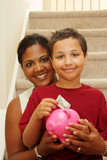 Woman And Son Holding Piggy Bank With Their Savings