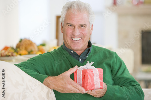 Senior Man Sitting On Sofa Holding A Christmas Gift